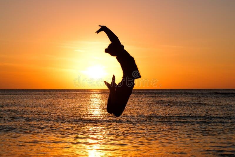 金黄日落的女孩在海滩 免版税库存照片