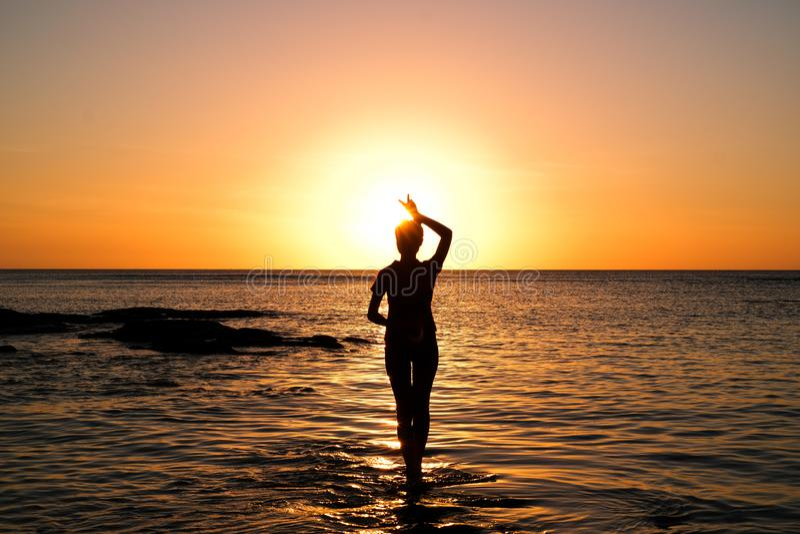 金黄日落的女孩在海滩 库存图片