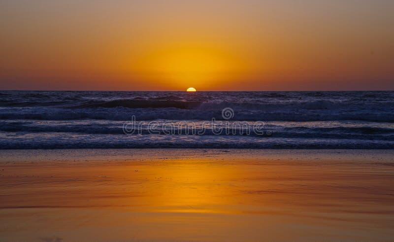 金黄日落,不安定的海,金黄海滩 库存图片