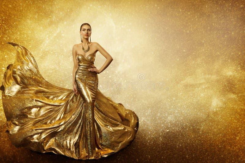 金黄时装模特儿,妇女飞行金礼服,挥动的褂子 免版税库存照片