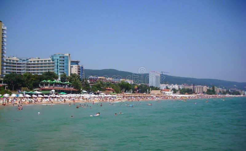 金黄沙子依靠,保加利亚- 2012年7月13日:游人获得在海边游泳的乐趣在黑海 库存照片