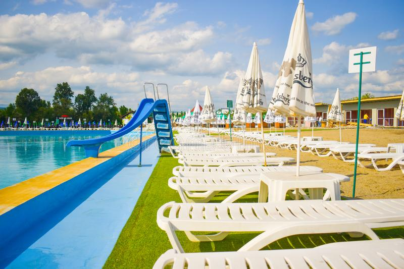 金黄沙子和白色海滩睡椅与伞在大游泳场附近子线的Ostroveni从Ramnicu瓦尔恰 罗马尼亚- 库存图片
