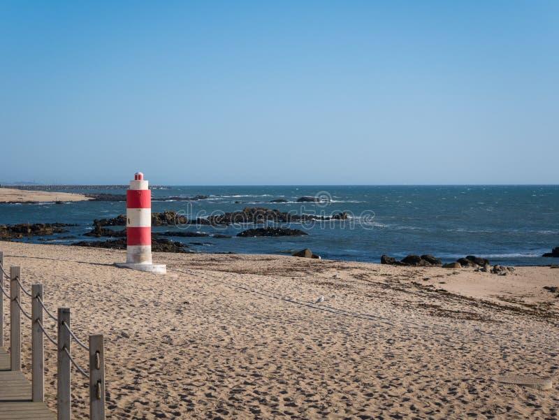 金黄沙滩灯塔和蓝天在波瓦-迪瓦尔津,波尔图,葡萄牙 免版税库存照片