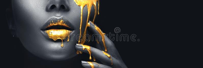 金黄油漆弄脏从面孔嘴唇和手,在美丽的模型女孩的嘴的金黄液体下落,创造性的构成的滴水 免版税图库摄影