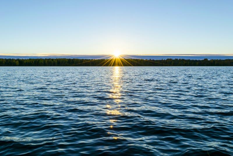 金黄波纹水面  与晚上天空的剧烈的金子日落天空覆盖在海  免版税库存图片