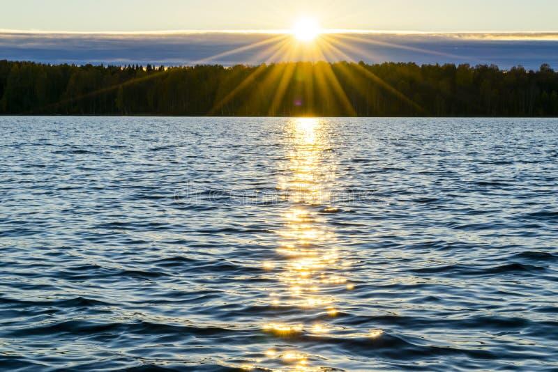 金黄波纹水面  与晚上天空的剧烈的金子日落天空覆盖在海  免版税库存照片
