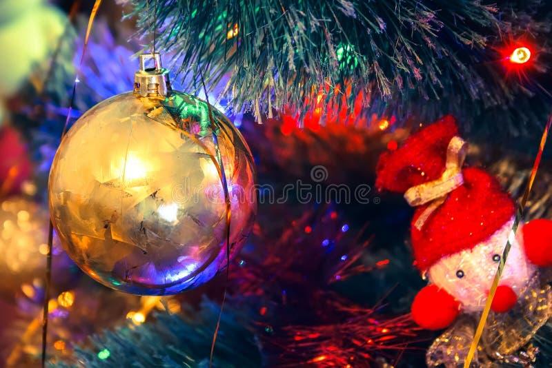 金黄球和被编织的玩具吊在一棵绿色圣诞树 免版税库存照片