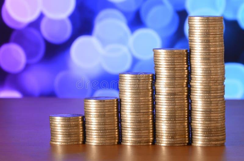 金黄硬币堆安排了作为图表 硬币的增长的专栏 免版税库存图片