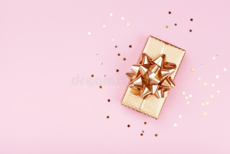 金黄礼物或当前箱子和星五彩纸屑在桃红色台式视图 生日、圣诞节或者婚礼的平的位置构成 免版税库存照片