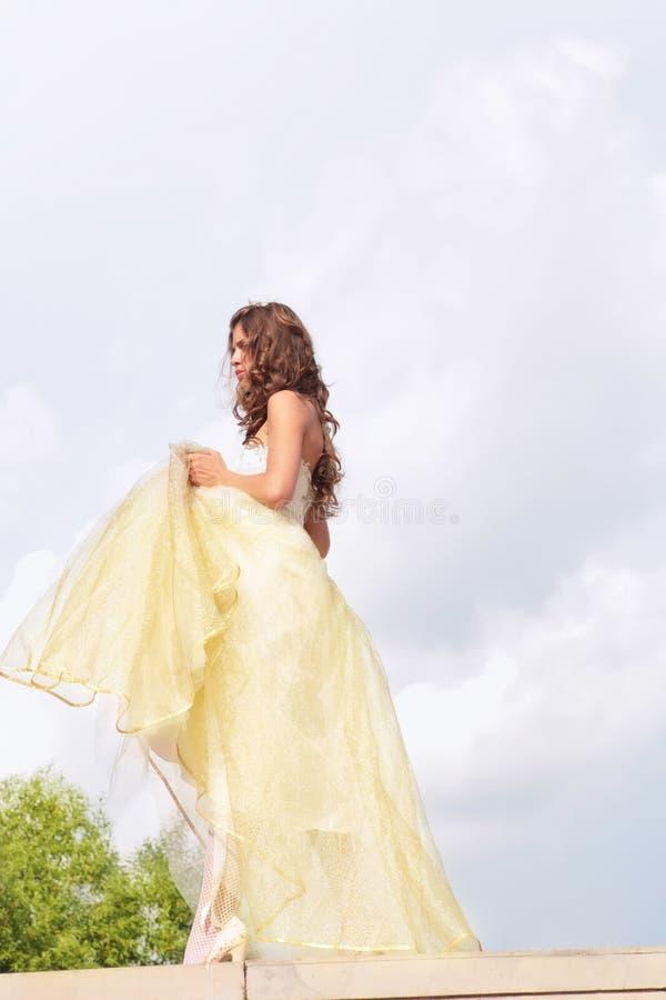 金黄美丽的礼服的女孩 图库摄影