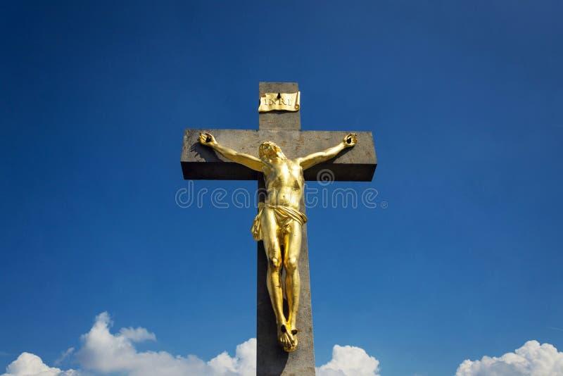 金黄耶稣基督在十字架上钉死雕象,晴朗的夏日蓝天背景 库存照片