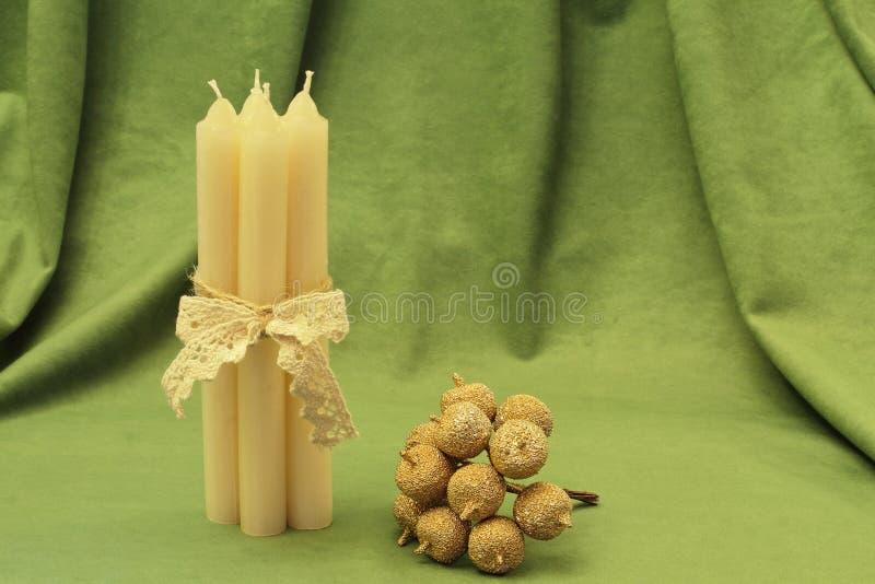 金黄苹果和白色蜡蜡烛装饰花束栓与在绿色背景的鞋带辫子 库存照片