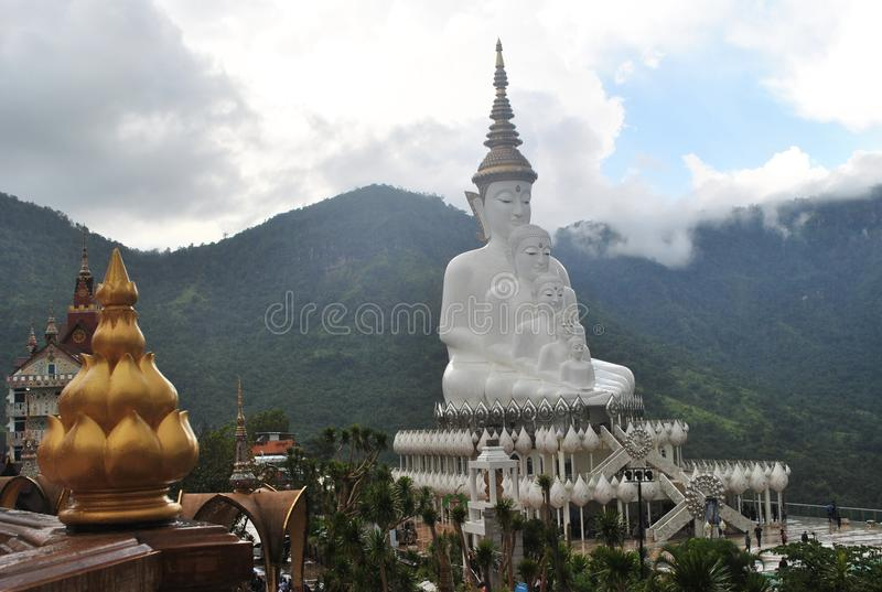 金黄莲花和白色佛教坐和凝思建筑学有背景山和云彩狂放的视图泰国 免版税库存图片