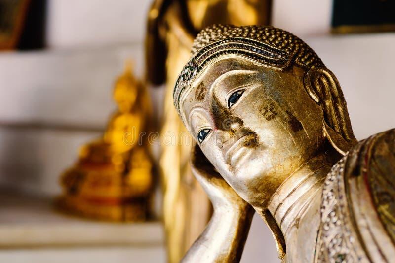 金黄菩萨雕象斜倚的接近的面孔 免版税库存图片