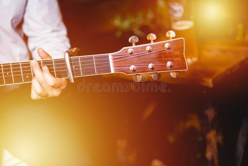 金黄蓝色 弹吉他,木墙壁背景,电或者声学吉他的歌手独奏声音妇女的人的男性手 库存照片
