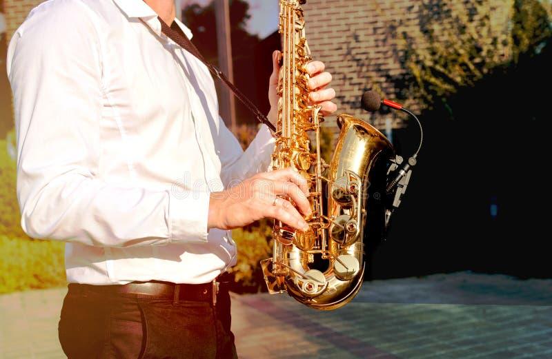 金黄蓝色 男孩结合萨克斯管部分在事件,爵士乐使用在萨克斯管,乐器的球员男性弹奏由人saxopho 免版税库存照片
