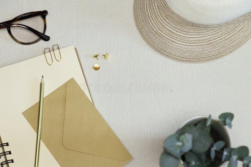 金黄被打开的笔记本、铅笔,纸夹、别针、信封、眼镜和帽子在桌上 图库摄影