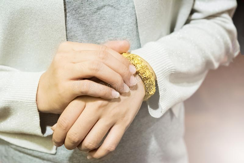 金黄镯子手镯装饰是与玫瑰色样式的下垂装饰品在妇女腕子在白光下 库存图片