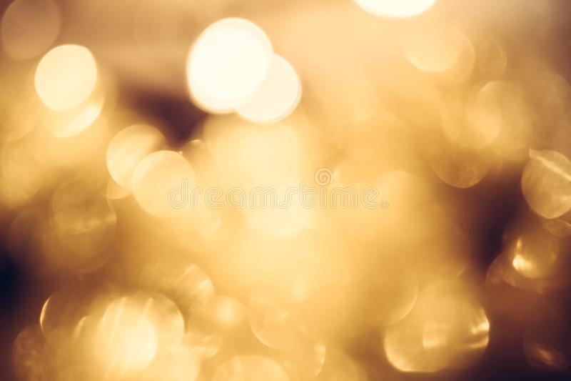 金黄黄色弄脏了光,与光亮的圣诞灯的欢乐温暖的bokeh在金子颜色当圣诞节背景 免版税库存图片
