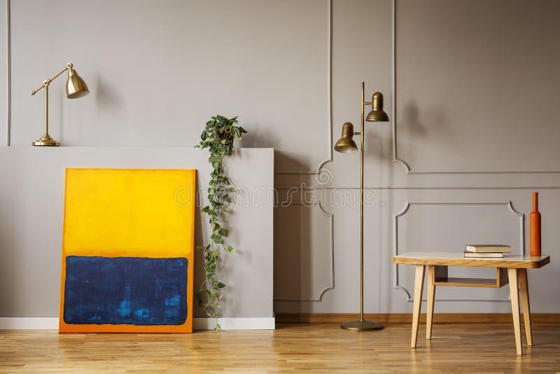 金黄黄铜落地灯、一张抽象绘画和一张木书桌在一个灰色客厅内部地方扶手椅子的 实际照片 库存照片