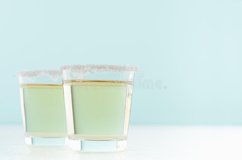 金黄龙舌兰酒茶点富有的酒精射击饮料与盐外缘的在白色和淡色绿色背景,拷贝空间 库存图片