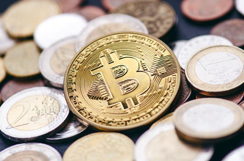 金黄bitcoin在与欧洲硬币的黑暗的背景铸造 真正货币 隐藏货币 新的真正金钱 透镜火光 图库摄影