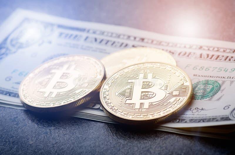 金黄bitcoin在纸美元金钱和黑暗的背景铸造与太阳 真正货币 隐藏货币 新的真正金钱 库存照片