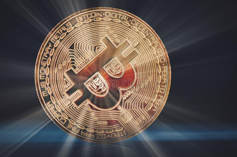 金黄bitcoin折除在轻轻地被点燃的黑暗的背景和光线的硬盘 免版税库存照片