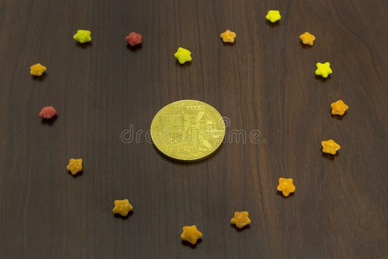 金黄bitcoin硬币后侧方在五颜六色的糖的担任主角 免版税库存照片