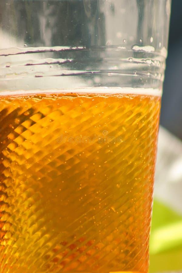 金黄啤酒、强麦酒或者贮藏啤酒在塑料一次性杯子 库存照片