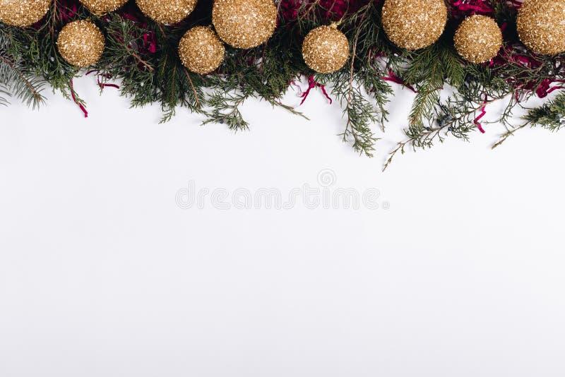 金黄圣诞节球和冷杉行在一白色backgr分支 免版税库存照片