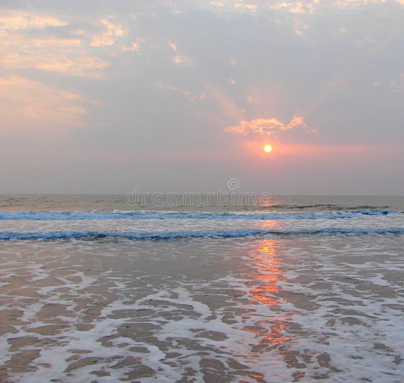 金黄太阳、阳光通过云彩和反射在海水的Payyambalam靠岸, Kannur,喀拉拉,印度 库存照片