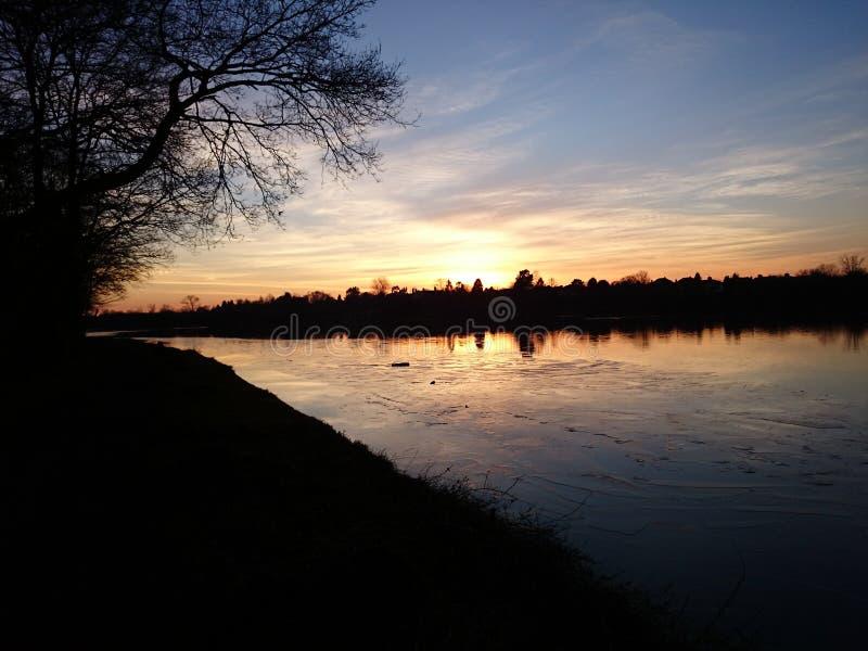 金黄太阳设置在冰寂静的结冰的湖的阶段  免版税库存图片