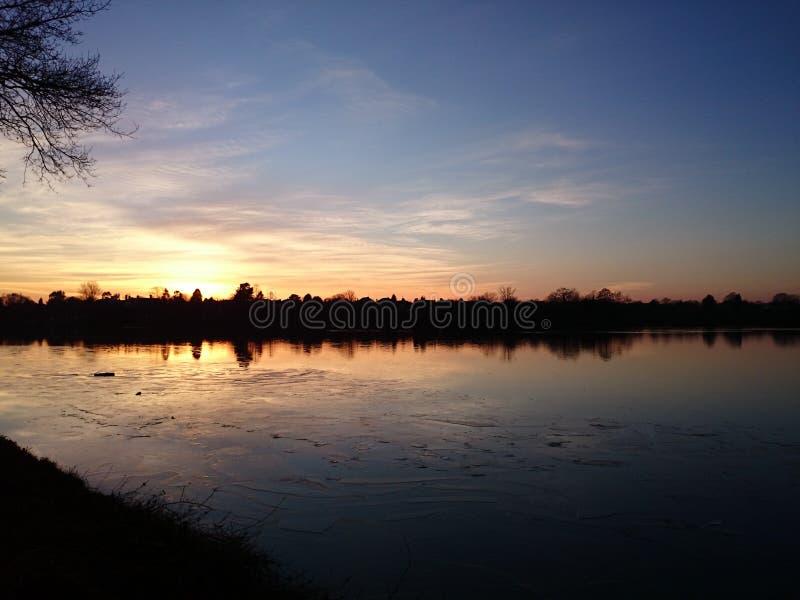 金黄太阳设置在冰寂静的结冰的湖的阶段  库存照片