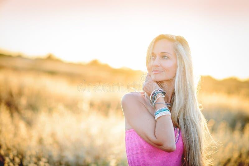 金黄干草领域的4一名美丽的妇女 免版税库存图片