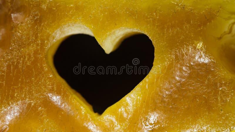 金黄琥珀特写镜头与心脏爱标志的作为背景 免版税库存图片