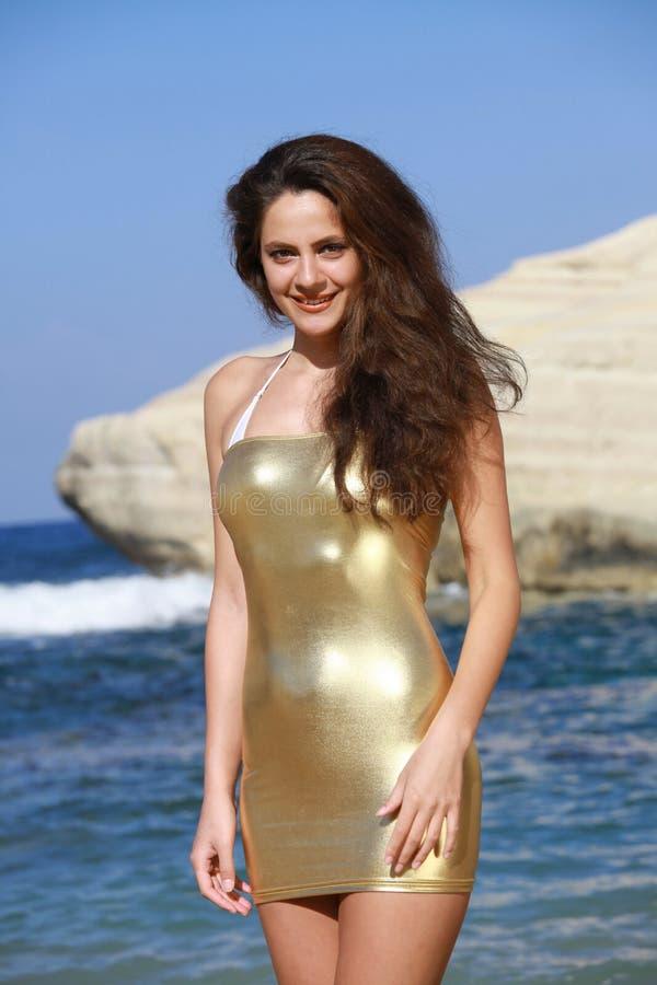 金黄礼服的女孩在海滩 库存图片