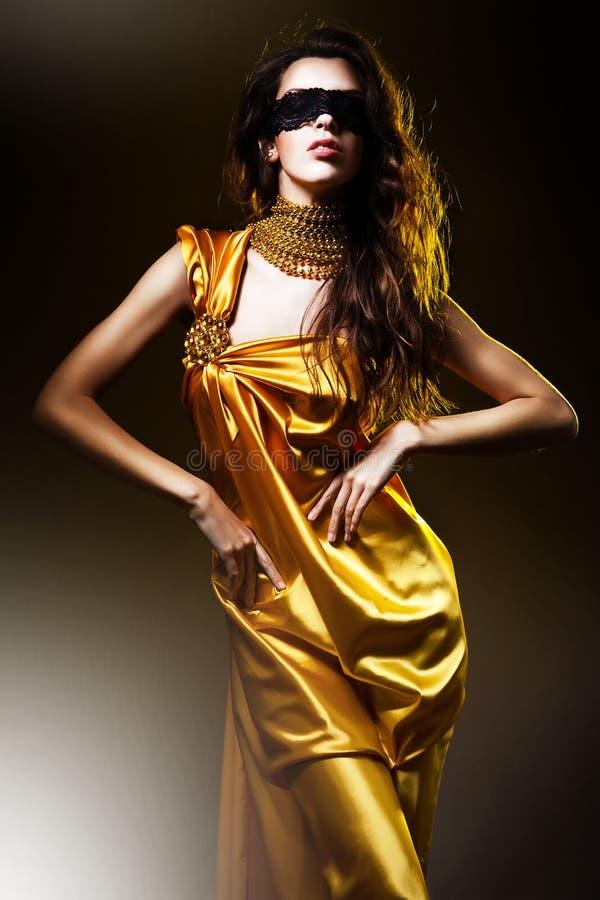 金黄礼服的肉欲的妇女 免版税库存图片