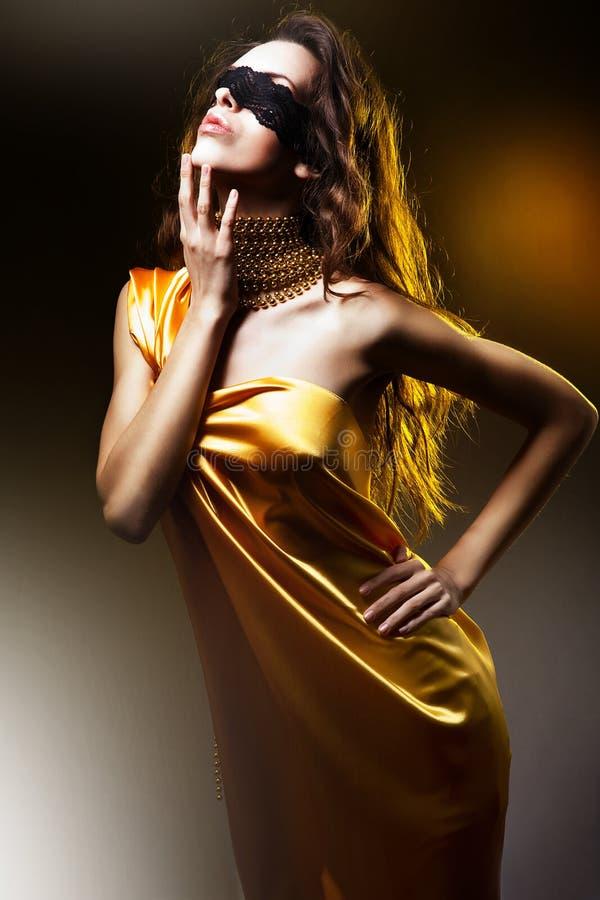 金黄礼服的肉欲的美丽的妇女 免版税图库摄影