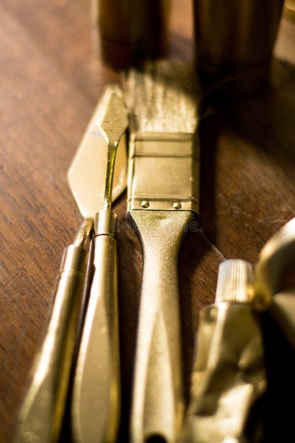 金黄色的刷子和小铲木表面上 库存照片