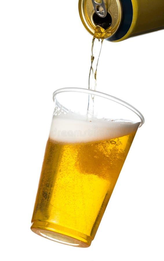 金黄贮藏啤酒或啤酒在一次性塑料杯子 免版税图库摄影