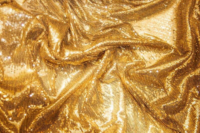 金黄衣服饰物之小金属片-闪耀的闪光金属片的纺织品 免版税库存照片