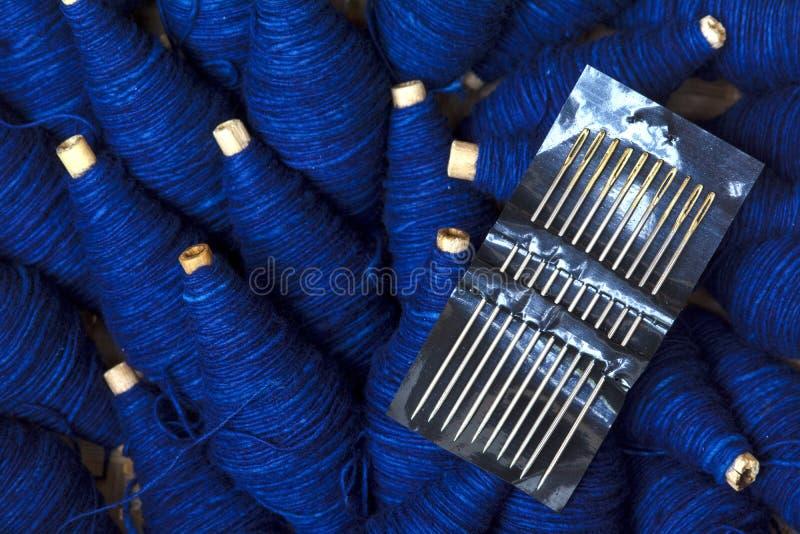 针和棉花螺纹套在小木核心背景 图库摄影