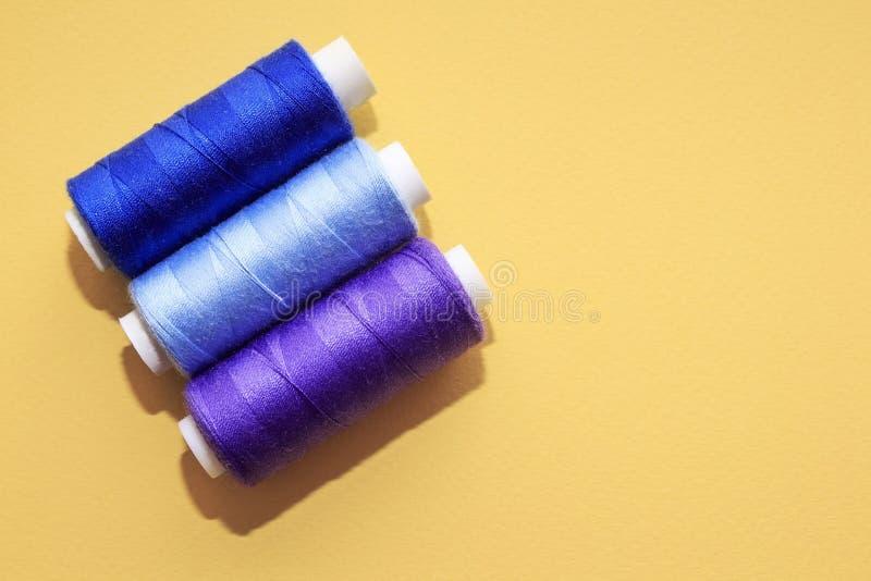 针线的概念,缝,刺绣 在黄色背景的缝合的多彩多姿的螺纹 库存照片