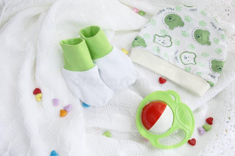 针织品新出生的婴孩赃物和帽子有五颜六色的吵闹声的在钩针编织的一揽子白色背景与五颜六色的心脏 免版税库存照片