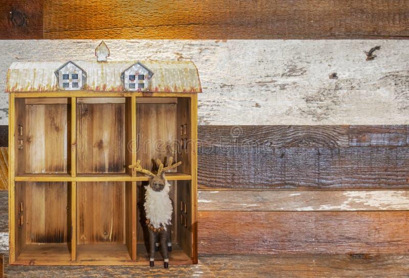 针felted与响铃的麋在立场在有罐子屋顶的装饰木谷仓对白色背景-拷贝的室的一边 库存图片