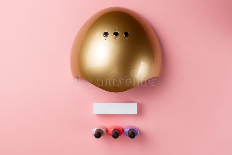 用于指甲的紫外线灯和用于粉色背景上修指甲和修脚的化妆品 顶视图 平铺 免版税库存照片