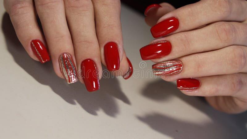 钉子设计用不同的衣服饰物之小金属片以在红色和桃红色钉子的心脏的形式为 库存照片