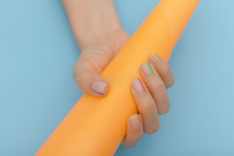 钉子设计 有多的collored修指甲的手在蓝色背景 女性手特写镜头有色的钉子的用桔子 库存图片