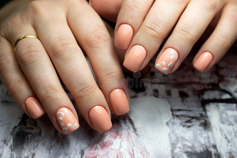 钉子设计 有明亮的橙色修指甲的手在紫罗兰色背景 关闭女性手用时髦桔子 艺术 免版税库存照片
